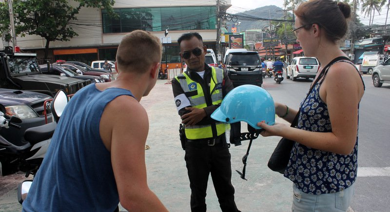 A rider being checked by a traffic police for not wearing the helmet while riding a motorbike in Phuket